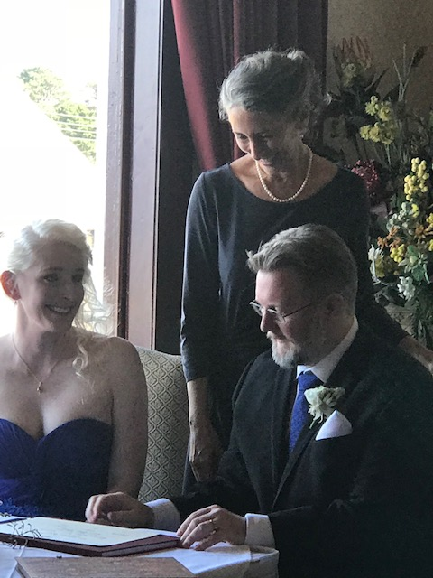 Emma and Andrew signing their wedding documents with Linda, the celebrant, at their wedding in the Blue Mountains.