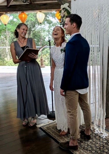Linda, as the celebrant with Vanessa and Patrick. The picture was taken during their wedding ceremony at Kalang, the valley next to Bellingen. Everyone is laughing.